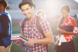 A yound college student in a plaid shirt carries his books and smiles laughingly with his friends