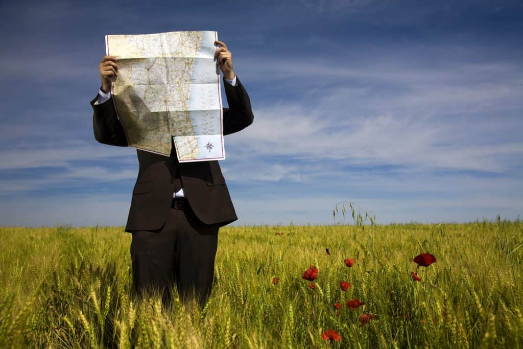 A person in a business suit in a field with a map