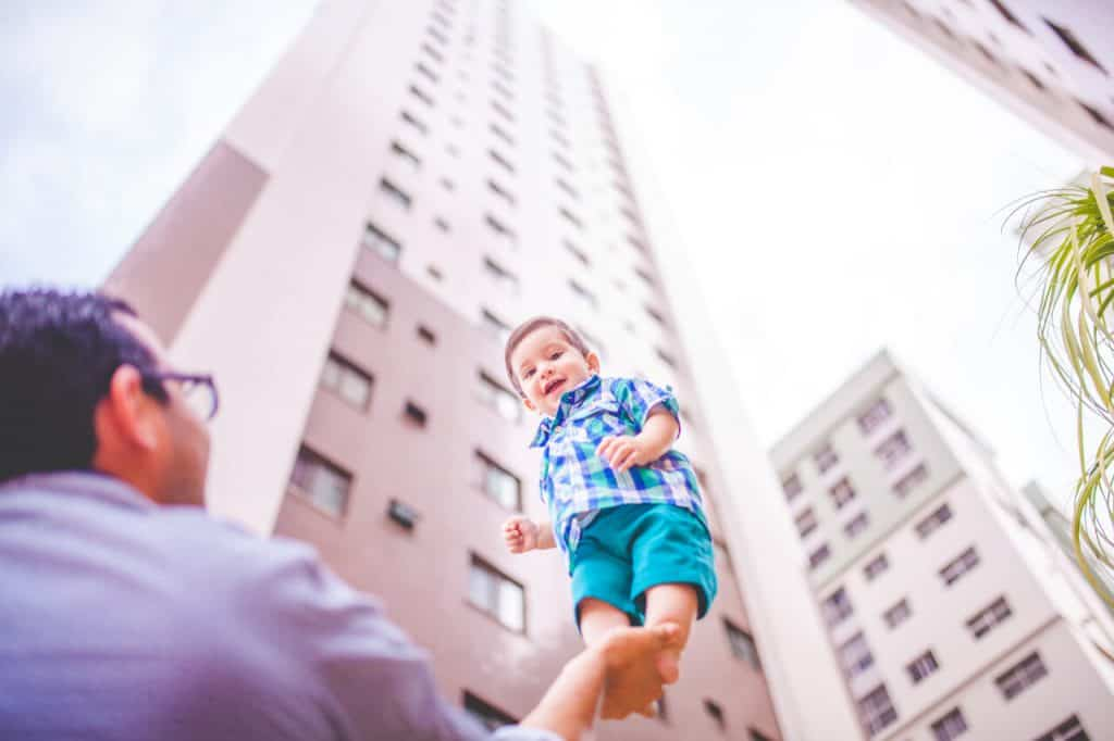 A bright-eyed young boy standing tall in the palm of his father as a skyscraper shoots into the sky in the background
