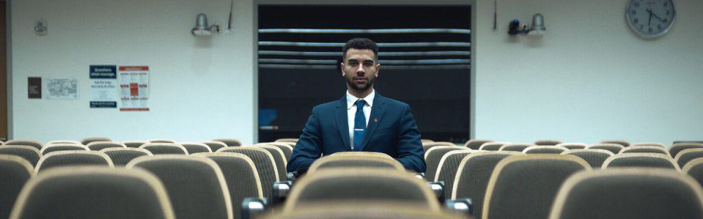 A man in a suit and tie sits at the center of a dim lecture hall, surrounded by empty seats