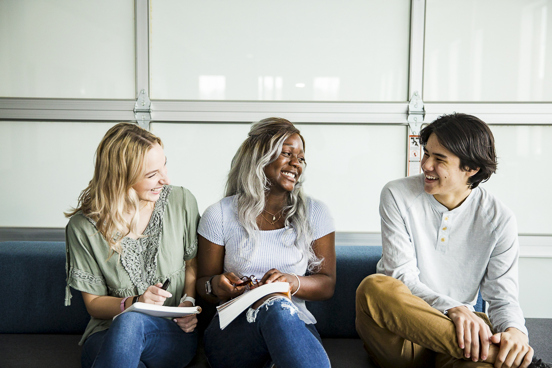 Three high school students sitting beside each other, laughing and chatting over their school notes