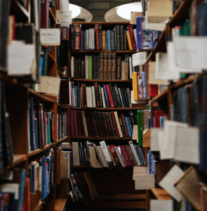 A narrow corridor of book-laden library shelves, various sections marked by out-reached fingers of book pages