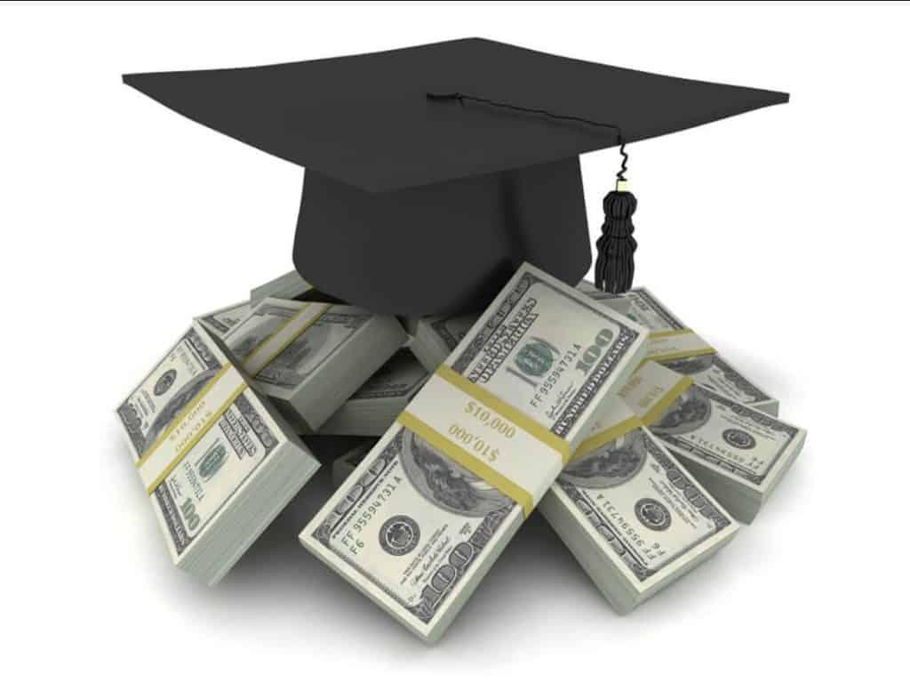 A graduation cap perched atop stacks of $100 dollar bills
